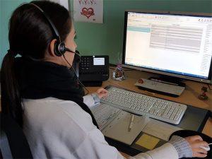 Frau mit Headset vor einem PC-Arbeitsplatz