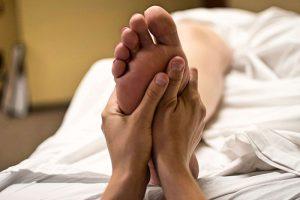 Fußreflexzonenmassagen, Zwei Hände bearbeiten einen Fuß