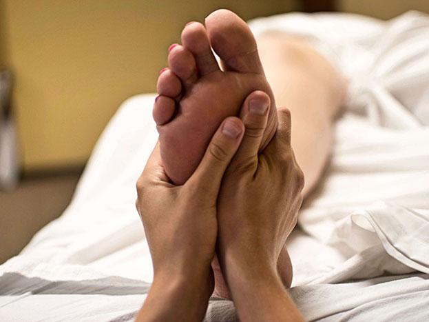 Zwei Hände bearbeiten einen Fuß