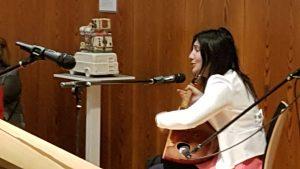 Frau mit Gitarre vor einem Mikrofon