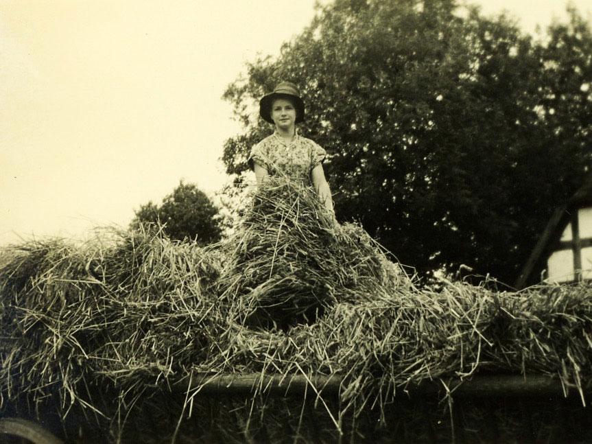 Sommerferien auf dem Bauernhof, Mädchen mit Hut auf einem Heuwagen