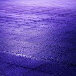 Nasse Gehwegplatten in blauem Licht