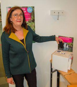 Handys recyceln, Eine Frau steckt ein Handy in eine Sammelbox
