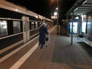 Alte Frau alleine auf einem Bahnsteig