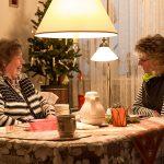 zwei Frauen sitzen sich gegenüber vor einem Weihnachtsbaum