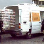 ein Gabelstapler hebt eine Palette mit Konserven in den LAderaum eines Kleintransporters