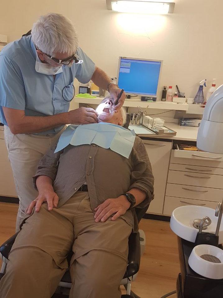 Zahnarzt untersucht einen liegenden Patienten