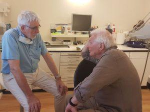 Zahnarzt sitzt vor einem Patienten auf dem Behandlungsstuhl