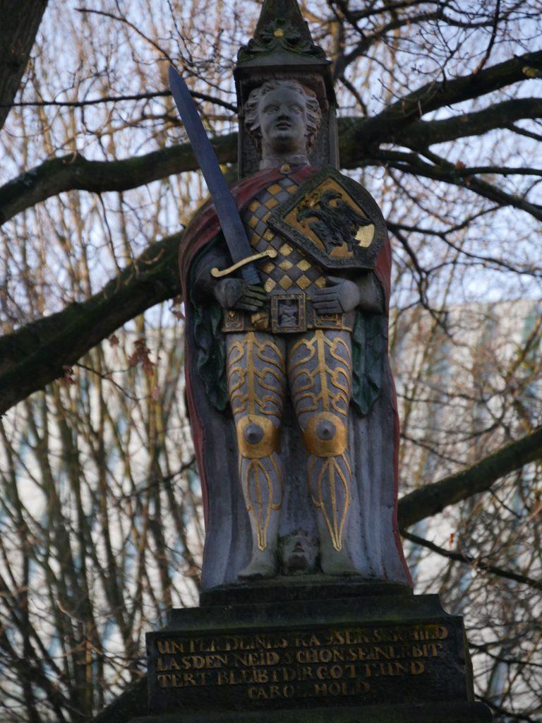 Steinerne Rolandfigur vor einem winterlichen Baum