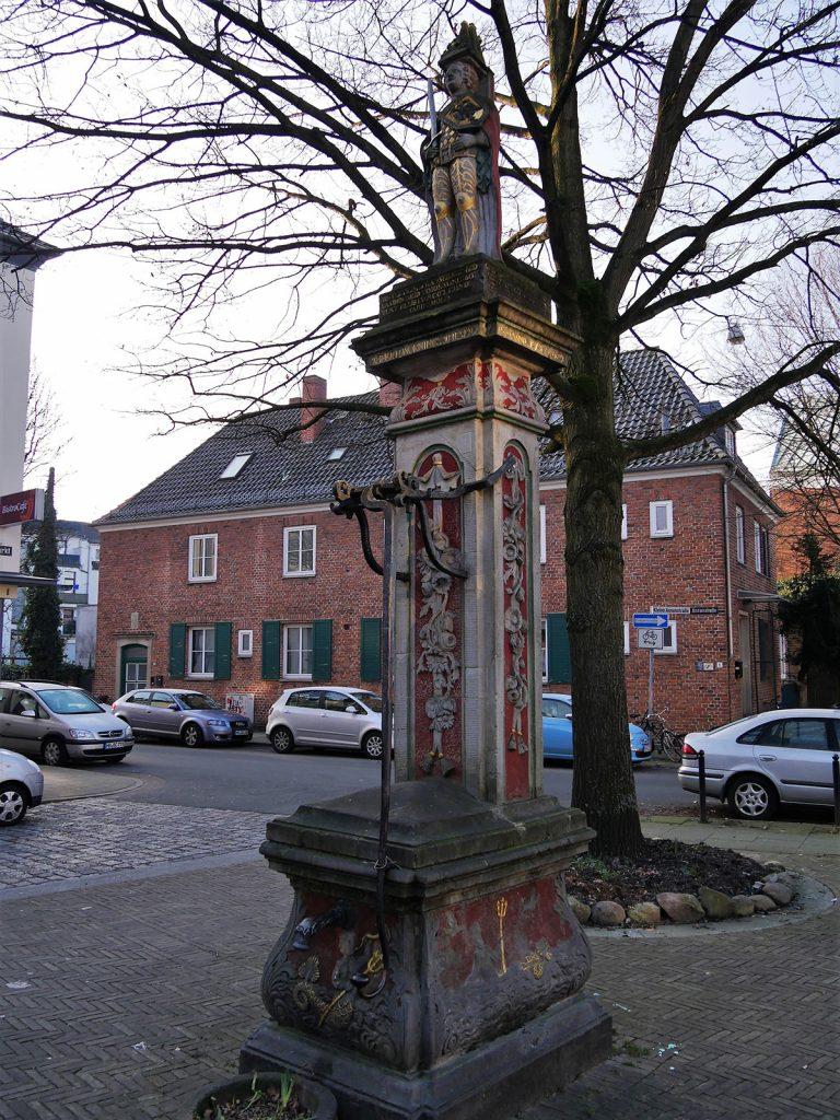 Platz mit steinerner Rolandfigur vor einem Backsteingebäude