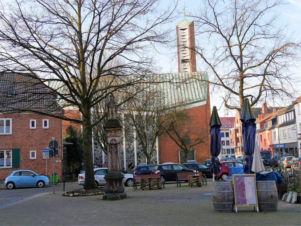 Platz mit steinerner Rolandfigur vor einer modernen Backsteinkirche