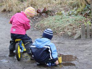 Geschwister, Zwei Kinder spielen an einer Pfütze
