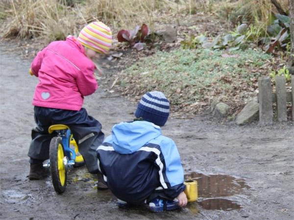 Zwei Kinder spielen an einer Pfütze