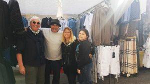 Wochenmarkt Mallorca, Vier Personen vor einem Verkaufsstand mit Bekleidung