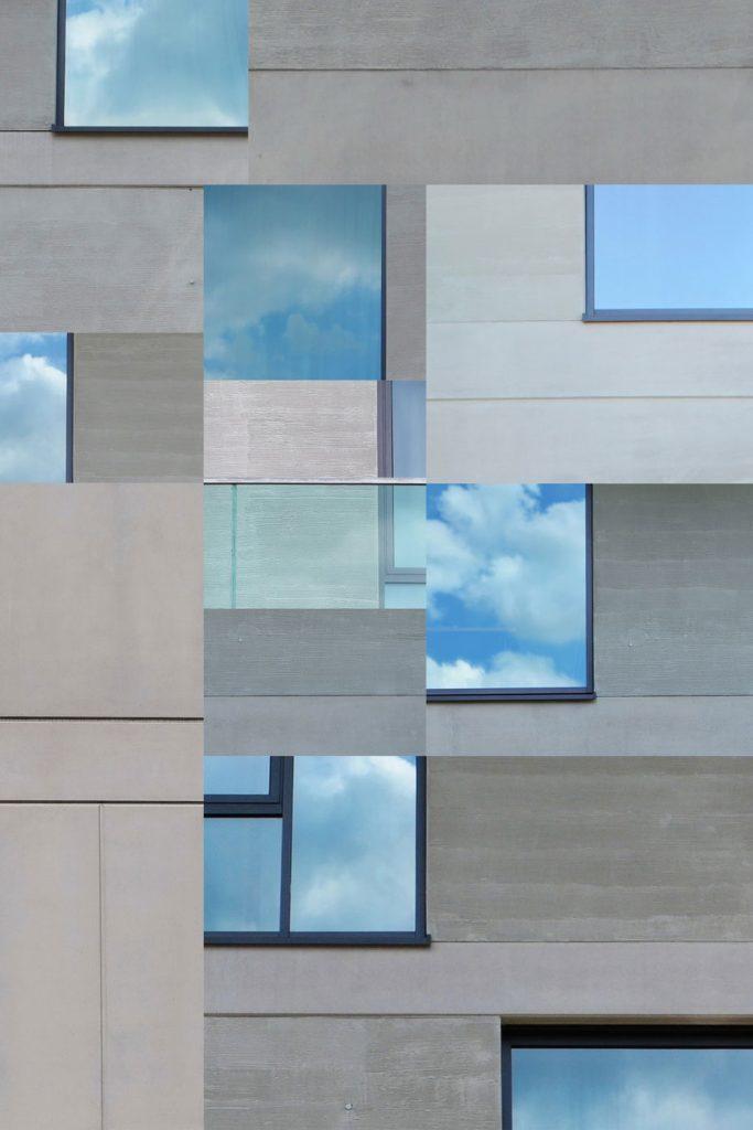 fassade eines modernen Gebäudes, in dessen Fenstern sich blauer Himmel spiegelt
