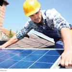 Arbeiter mit gelbem Helm hält ein Segment einer Photovoltaikanlage