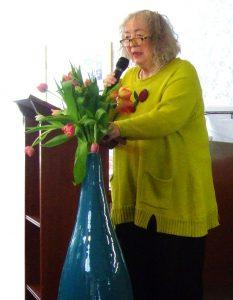 Annelie Keil, Frau am Rednerpult mit Blumen im Vordergrund