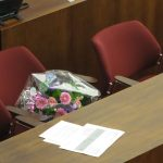 Zwei Stühle und ein Tisch in der Bürgerschaft. Auf einem Stuhl liegen Blumen bereit