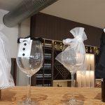 Weinflaschen und Weingläser mit Hochzeitsschmuck