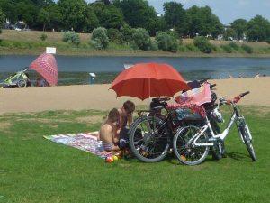 Menschen unter Sonnenschirm am Flussufer mit Fahrrädern