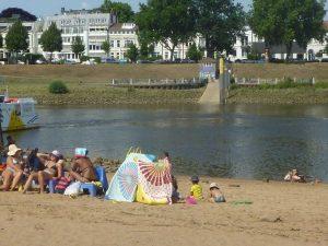 Blick auf Fluss mit Badegästen
