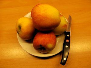 Teller mit Äpfeln und bstmesser